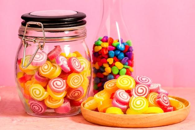 Süßigkeit und gelee bunt in der holzschale auf rosa hintergrund