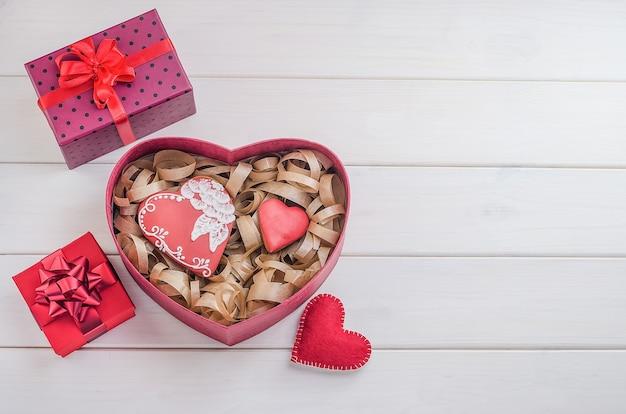Süßigkeiten als geschenk zum valentinstag. lebkuchen in form von herzen mit geschenken mit roten bändern mit kopienraum auf einem weißen hölzernen hintergrund. kochen, backen .-