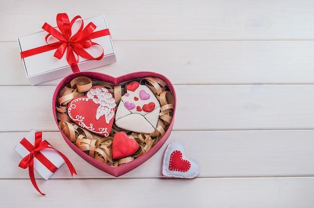 Süßigkeiten als geschenk zum valentinstag. lebkuchenplätzchen in form von herzen und einem umschlag mit weißen geschenken mit roten bändern mit kopienraum auf einem weißen hölzernen hintergrund. kochen, backen.