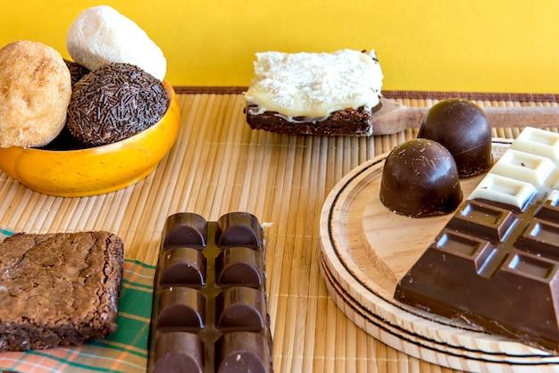 Süßigkeiten auf dem tisch. schokoladenkuchen, kekse, brownie und schokoriegel. ansicht von oben.