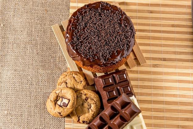 Süßigkeiten auf dem tisch. schokoladenkuchen, kekse und schokoriegel. ansicht von oben.