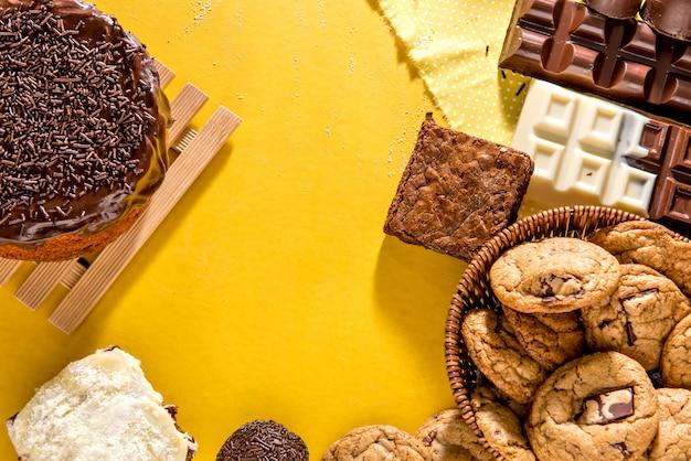 Süßigkeiten auf gelbem hintergrund. schokoladenkuchen, kekse, brownie und schokoriegel. ansicht von oben.
