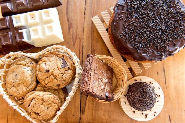 Süßigkeiten auf hölzernem hintergrund. schokoladenkuchen, kekse, brownie und schokoriegel. ansicht von oben