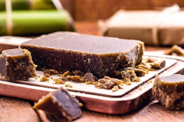 Süßigkeiten aus braunem zuckerriegel und stücken, süßigkeiten aus zuckerrohrmelasse auf einem rustikalen holztisch
