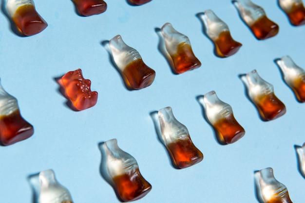 Süßigkeiten, die süßigkeiten in flaschenform über blauem hintergrund kauen.