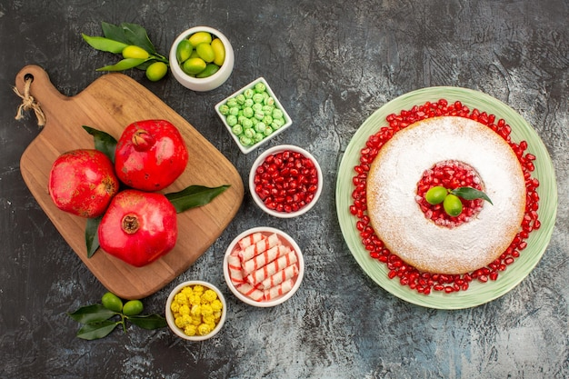Süßigkeiten ein appetitlicher kuchen süßigkeiten granatäpfel auf dem schneidebrett zitrusfrüchte