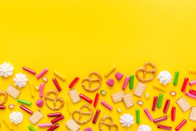 Süßigkeiten flach legen auf gelben hintergrund