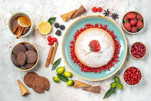 Süßigkeiten kekse eine tasse tee einen kuchen zimtstangen beeren zitrusfrüchte