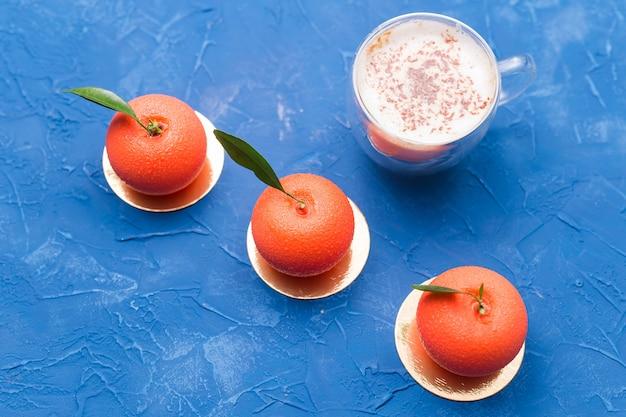 Süßigkeiten, kuchen und leckeres konzept - mousse-dessert in form einer orangenfrucht. tasse kaffee zum frühstück