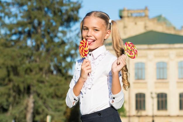 Süßigkeiten machen den mund glücklich. kleines mädchen lecken süßigkeiten im freien sonnig. süßigkeitenladen. lutscher oder sauger. zuckerhaltiger genuss. süßwaren. essen und snacks. süße welt. du verdienst heute eine süßigkeit.