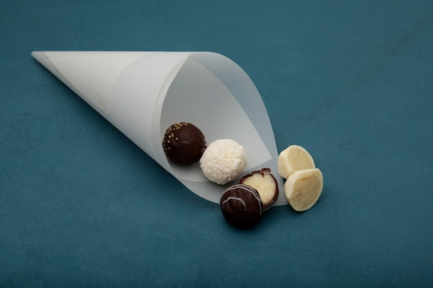 Süßigkeiten mit käsefüllung in papierkegel auf blau