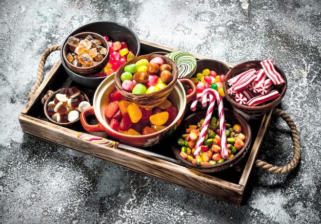 Süßigkeiten süßigkeiten, kandierte früchte mit marshmallow und gelee auf einem holztablett.