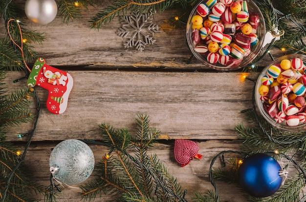 Süßigkeiten, weihnachtskugeln und fichtenzweige auf einer holzoberfläche