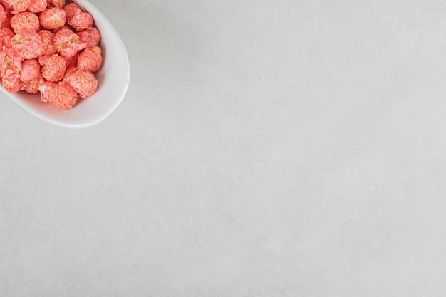 Süßigkeitenhalter mit rotem popcorn auf marmortisch bestückt.