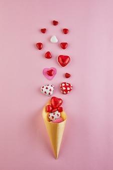 Süßigkeitenherzen fliegen aus einer eistüte auf einer rosa oberfläche.