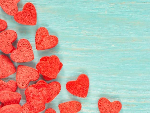 Süßigkeitsherzkonfetti auf blauem hölzernem hintergrund