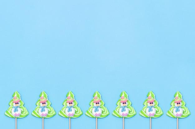Süßigkeitslutscher lustige schneemänner und weihnachtsbaum auf blauem hintergrund.