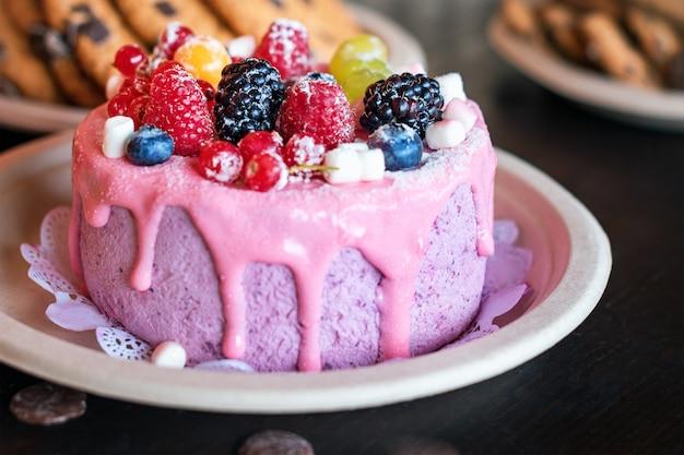 Süßkäsekuchen mit frischen beeren und joghurtcreme. köstlicher himbeerkuchen mit frischen erdbeeren, himbeeren, blaubeeren, johannisbeeren und brombeerfrüchten auf rustikaler holzoberfläche