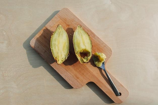 Süßkartoffel halbiert mit teelöffel auf holzbrett