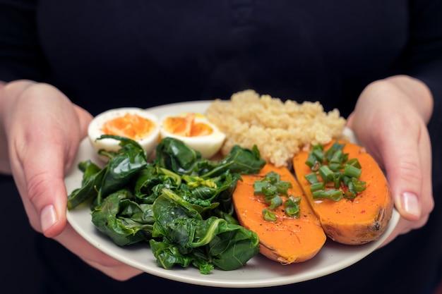 Süßkartoffel mit quinoa, gekochtes ei auf teller in den händen der frau