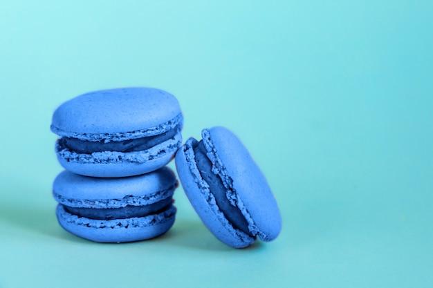 Süßmandel macaron oder makronen dessert kuchen in trendigen farbe des jahres 2020 classic blue isoliert auf blauem pastell hintergrund gefärbt. makro mit farbe. copyspace.