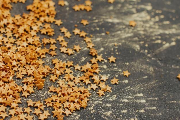 Süßwaren konfetti in form von goldenen sternen auf einem dunkelgrauen hintergrund