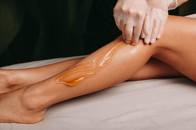 Sugaring epilation in einem spa-salon von einem jungen fachmann während eines eingriffs durchgeführt