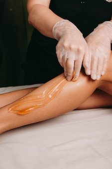 Sugaring-verfahren an den beinen durch einen spa-spezialisten während eines eingriffs im salon