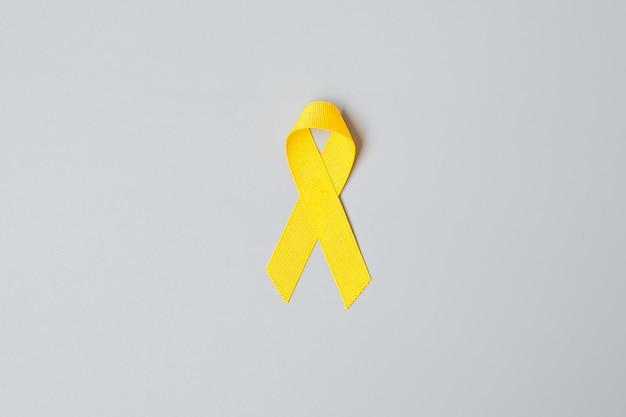 Suizidprävention, sarkom, knochen, blase, monat der aufklärung über krebs im kindesalter, gelbes band zur unterstützung von leben und krankheit. kindergesundheits- und weltkrebstagkonzept