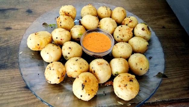Suji appe oder reis appe oder appam, ein indischer snack mit zwiebeln, erdnüssen und tamarinden-dip in indien