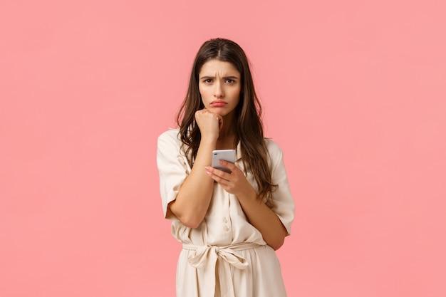 Sulky süße freundin vor komplizierten entscheidung, stirnrunzeln und schmollen auf die faust gelehnt, smartphone halten, seltsame nachricht lesen kann nicht verstehen