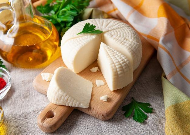 Suluguni-käse wird auf einem holzbrett in große stücke geschnitten. garniert mit petersilienblättern. im hintergrund ist eine flasche mit olivenöl und petersilie. auf grauem leinenhintergrund.