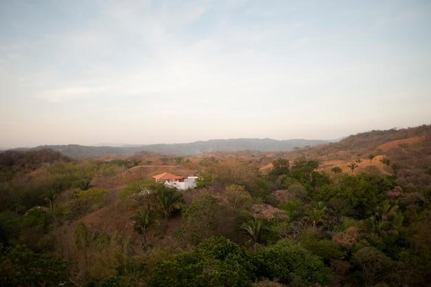Sun, der über einem weißen haus mit einem orange dach in den rolling hills über den treetops von costa rica verbläßt
