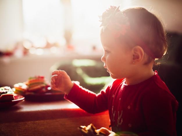 Sun macht heiligenschein um kleines mädchen mit keks in ihrem arm