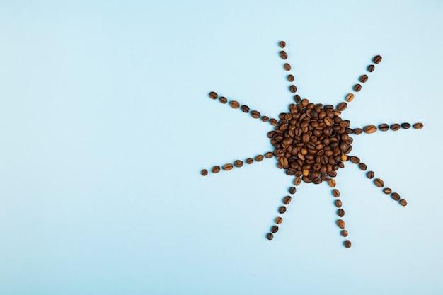 Sun machte von den kaffeebohnen auf blauem hintergrund. konzept beginnt morgens mit kaffee. draufsicht, exemplar