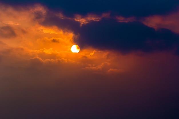 Sun mit dunklen wolken im orange himmel am abend mit korn