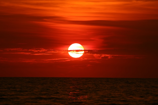 Sun zurück auf sonnenunterganghimmel-horizontwelle auf oberflächenmeer