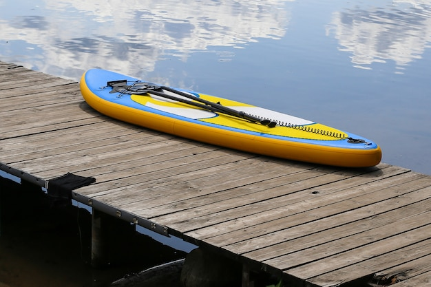 Sup board, stand up paddle board in der nähe des flusses am pier