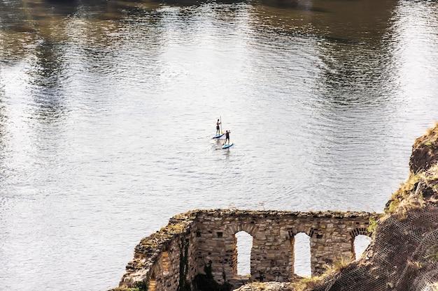 Sup boarding männer im vitava fluss, blick von den ruinen von libuses bad