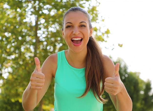 Super frau! porträt des gewinnermädchens, das daumen hoch zeigt. positive lächelnde fitness gesunde frau im freien.