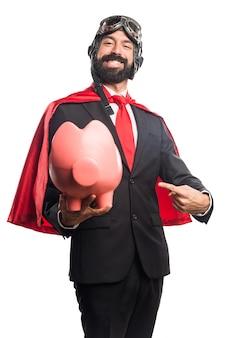 Super helden geschäftsmann hält ein sparschwein