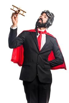 Super helden geschäftsmann mit einem hölzernen spielzeug flugzeug