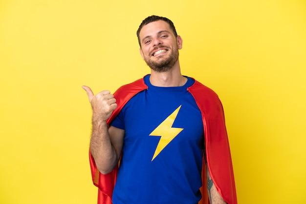 Super hero brasilianer isoliert auf gelbem hintergrund, der auf die seite zeigt, um ein produkt zu präsentieren