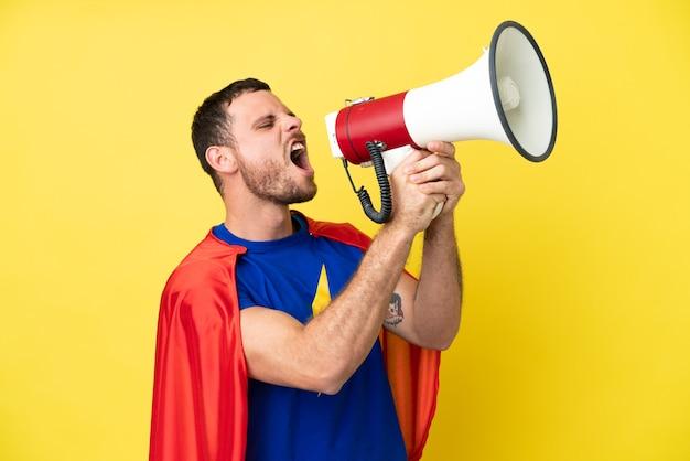 Super hero brasilianer isoliert auf gelbem hintergrund, der durch ein megaphon schreit
