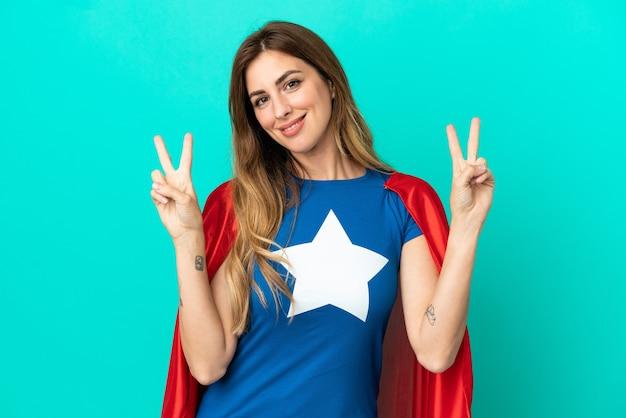 Super hero kaukasische frau isoliert auf blauem hintergrund mit victory-zeichen mit beiden händen