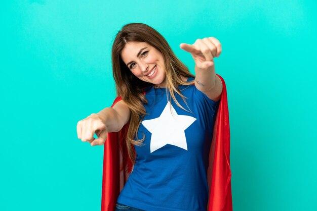 Super hero kaukasische frau isoliert auf blauem hintergrund zeigt mit dem finger auf dich, während sie lächelt