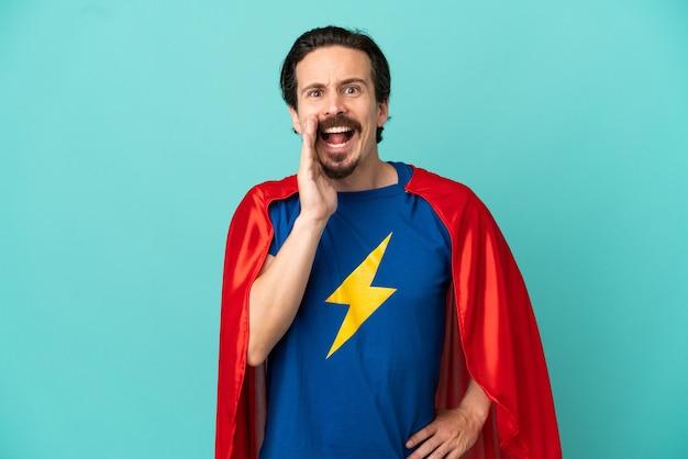 Super hero kaukasischer mann isoliert auf blauem hintergrund schreien mit weit geöffnetem mund