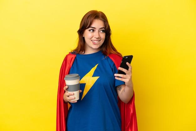 Super hero rothaarige frau isoliert auf gelbem hintergrund, die kaffee zum mitnehmen und ein handy hält, während sie etwas denkt