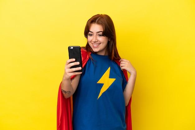 Super hero rothaarige frau isoliert auf gelbem hintergrund macht ein selfie