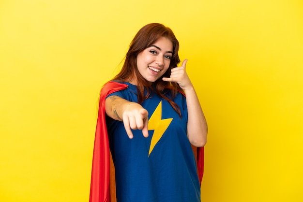 Super hero rothaarige frau isoliert auf gelbem hintergrund macht telefongeste und zeigt nach vorne